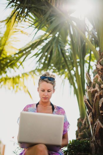 A beautiful woman working remotely in a tropical environment Wireless Technology Plant Technology Computer One Person Tree Communication Connection Real People Front View Nature Growth Day Using Laptop Leisure Activity Laptop Lifestyles Sunlight Women Outdoors Hairstyle Lens Flare Resort Working Remotely Mexico