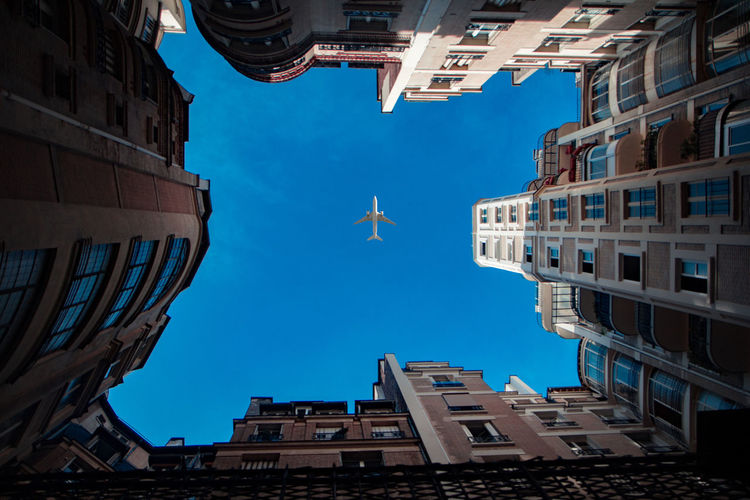 Low angle view of airplane flying over buildings against blue sky