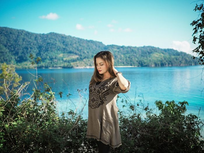 Young woman standing by lake against sky
