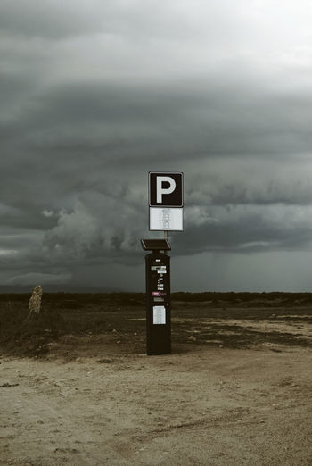 parking meter in the middle of nowhere Absence Beach Cloudy Day Deserted Extreme Weather Isolation Middle Of Nowhere Nature No People Non Urban Scene Out Of Context Outdoors Overcast Parking Parking Lot Parking Meter Sand Sign Sky Storm Cloud Vertical