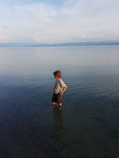 Boy Standing In Sea Against Sky