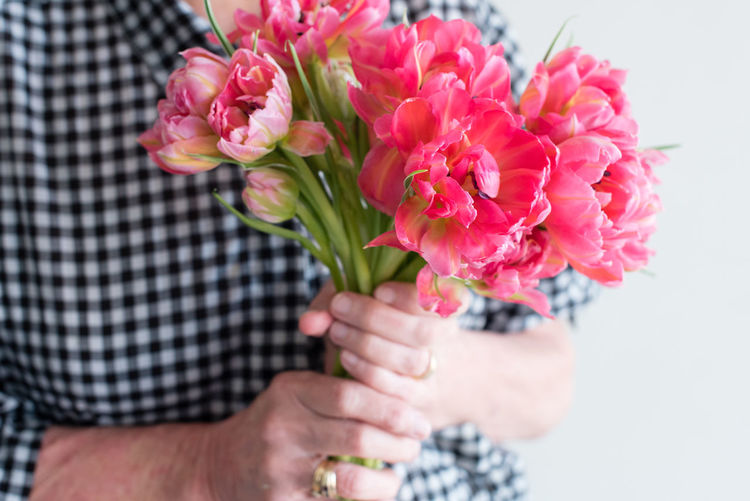 Woman in black and white shirt holding pink double tulips Adult Beauty In Nature Bouquet Close-up Day Flower Flower Head Fragility Freshness Holding Human Hand Nature One Person Outdoors People Petal Pink Color Real People Red Tulip Women