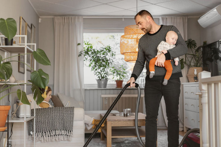 Full length of father holding baby at home
