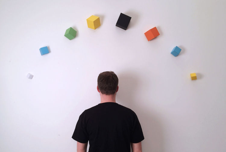 Rear view of man standing by wall with colorful blocks