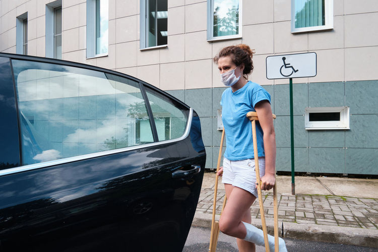A woman with an injured leg gets into a car. orthopedic plaster, orthopedic crutches.