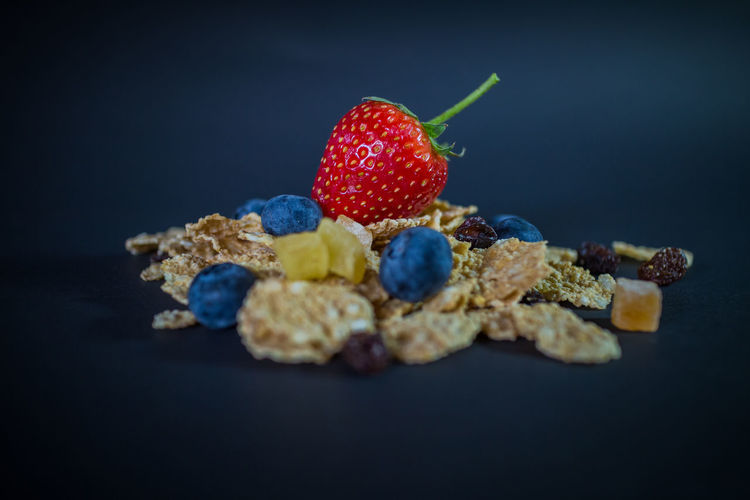 Close-up of fresh fruits in plate against black background