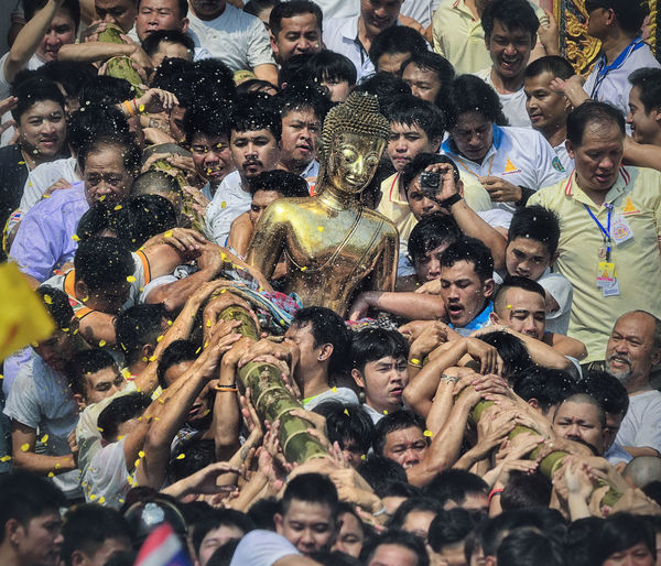 People Carrying Buddha Statue During Traditional Festival