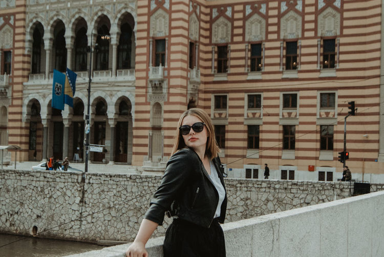Young woman wearing sunglasses while standing against buildings in city