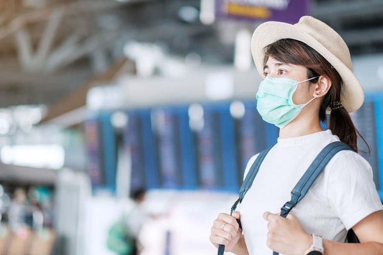 Woman with mask looking away in airport outdoors