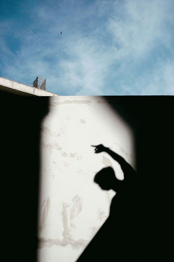 Shadow Of Man On Wall Against Sky