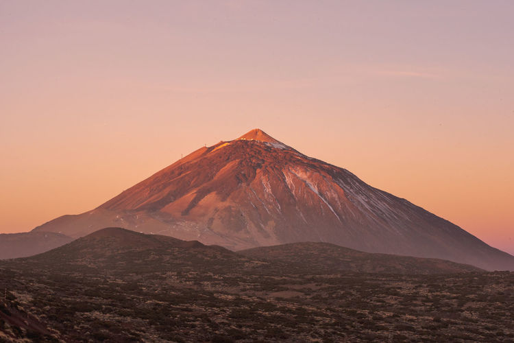 Scenic view of volcanic mountain during sunset