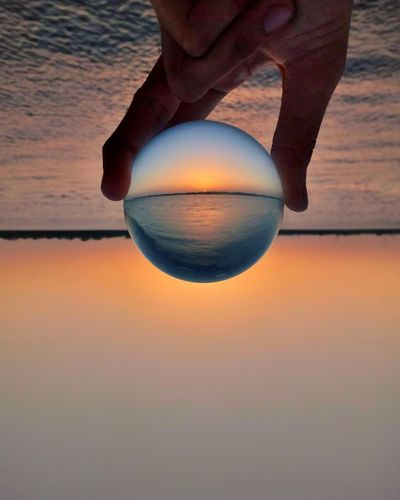 Midsection of person holding crystal ball against sky during sunset
