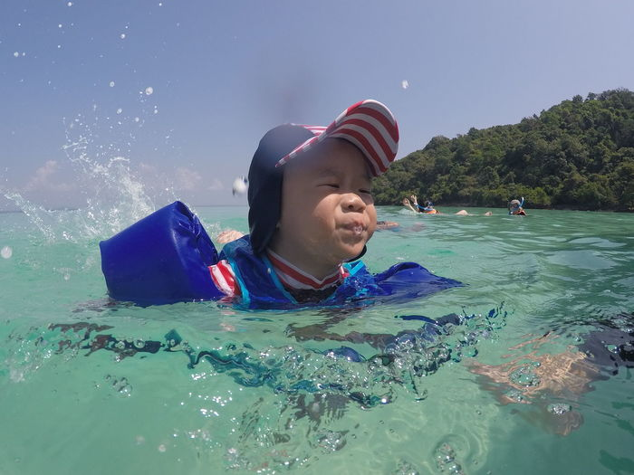 Close-Up Of Boy Swimming In Sea