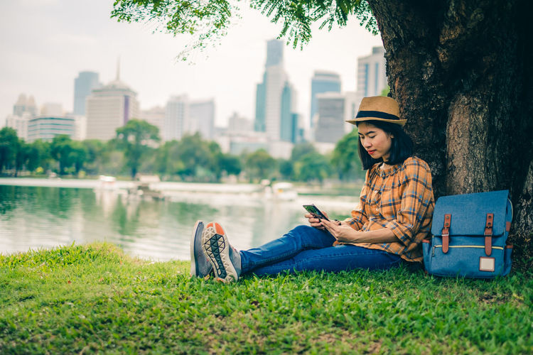 Young woman using mobile phone while sitting by tree