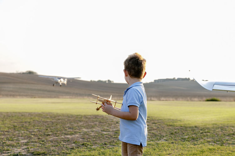 Side view of boy holding airplane on field against sky