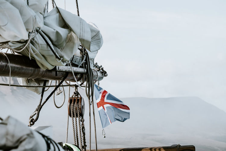 Flag flying form the deck of an old wooden schooner sailing ship Nautical Equipment Rope Sailing Ship Aboard Ship Day Deck Flag Mast Nature Nautical Vessel No People Outdoors Sailing Schooner Sea Sky