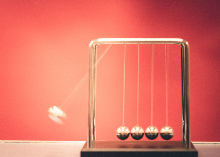 Creative image of a Newton's Cradle in motion Motion Blur Newton Cradle Physics Swinging Balls Close-up Cradle  Day Indoors  Metal Ball Metal Balls Motion Motion Capture Motion Photography Newtons Cradle No People Red Background Table