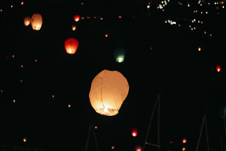Low angle view of illuminated lantern against sky at night
