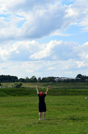 Woman With Arms Raised Standing On Field Against Sky