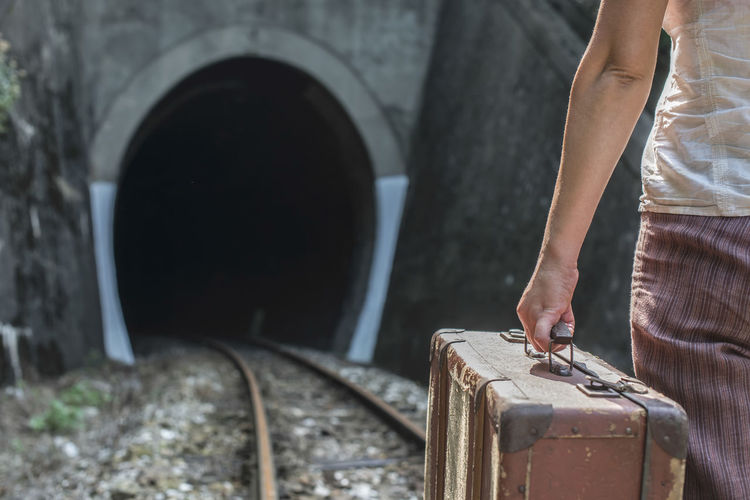 Travel Tunnel Railing Railway Rails Woman Suitcase Vintage One Person Real People Rail Transportation Human Body Part Standing Day Focus On Foreground Hand Human Hand Lifestyles Architecture Track Outdoors Railroad Track Men Transportation Midsection Journey Human Limb