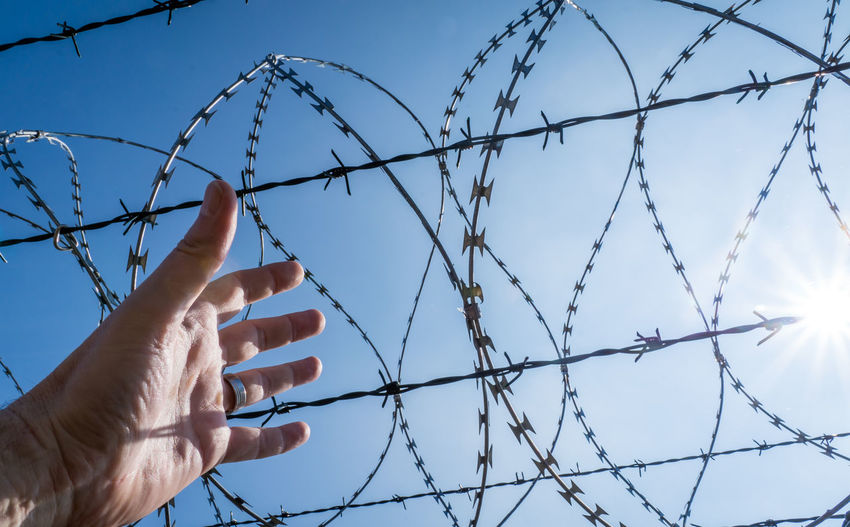 Cropped hand gesturing against razor wire