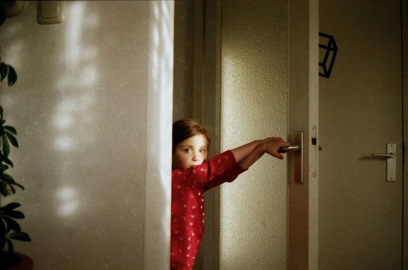 Portrait Of Girl Holding Door