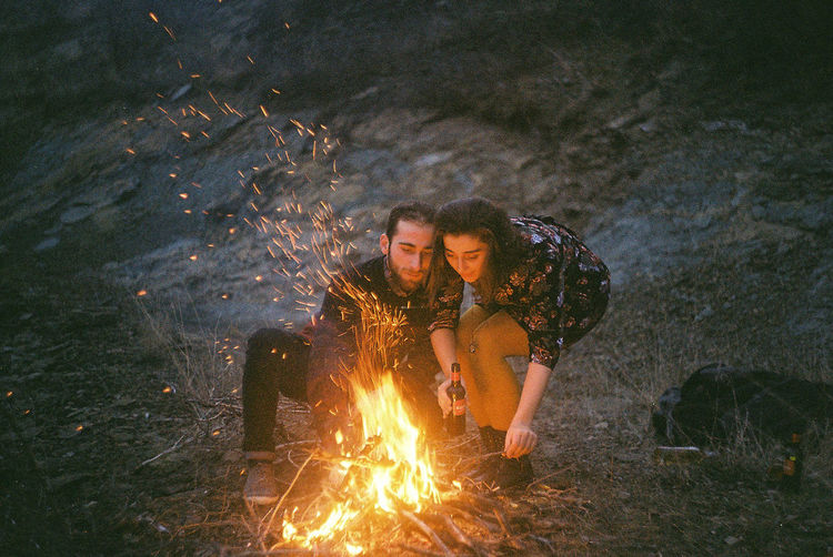 Couple Burning Campfire At Field