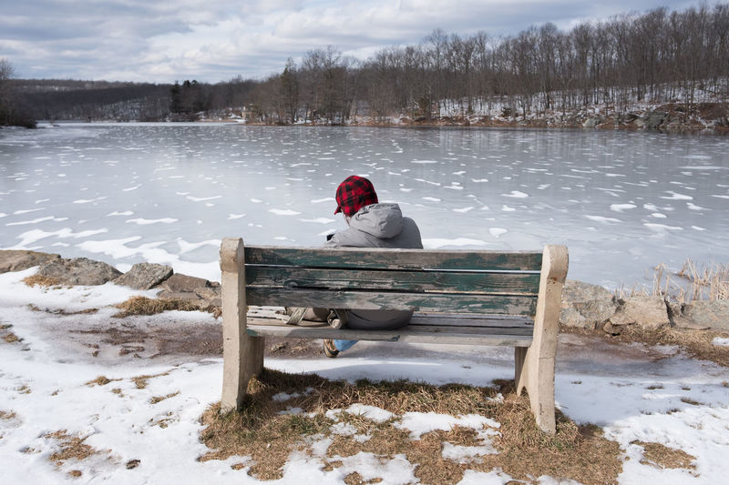 Man Sitting On Bench By Frozen Lake Against Sky During Winter