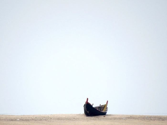 Abandoned boat on shore against clear sky
