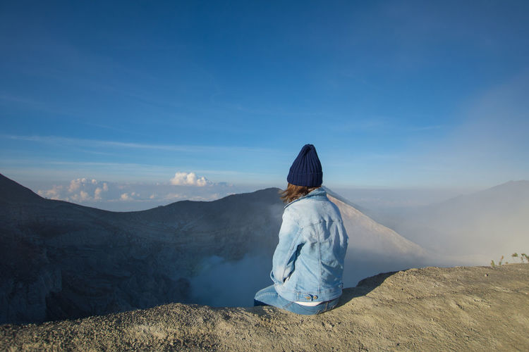 INDONESIA Adult Beauty In Nature Clothing Hairstyle Kawah Ijen Landscape Leisure Activity Lifestyles Looking At View Mountain Mountain Range Nature Non-urban Scene One Person Outdoors Real People Rear View Scenics - Nature Sitting Sky Sunlight Tourism Tranquil Scene Tranquility Travel Destinations Women