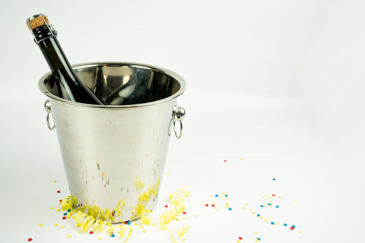 a bottle of champagne in a metal bucket on a white background Indoors  Studio Shot Food And Drink Close-up Still Life White Background Refreshment Copy Space Table Glass - Material Focus On Foreground Multi Colored Bottle Glass Temptation Confetti Metal Bucket Bucket Champagne Bottle Champagne Yellow Drink Alcohol Backgrounds Wallpaper
