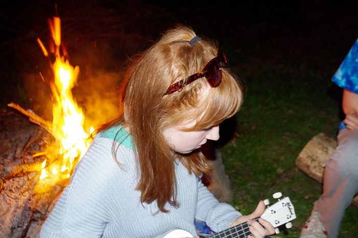 Camp Fire Camping Casual Clothing Close-up Enjoying Life Fire Focus On Foreground Fun Ginger Happy Illuminated Leisure Activity Lifestyles Outdoors Part Of Portrait Singing By The Fire Sunglasses Ukelele