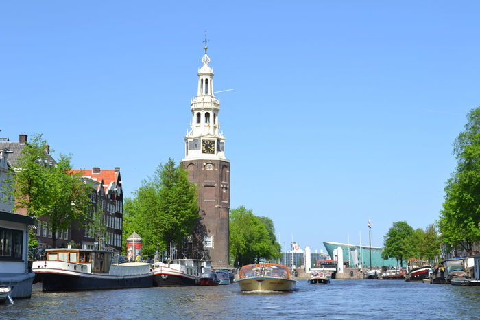 View of a canal in Amsterdam, The Netherlands Amsterdam Amsterdam City Architecture Blue Building Exterior Built Structure Clear Sky Day Holland Jordaan Moored Nautical Vessel Outdoors Place Of Worship Sky The Netherlands Transportation Tree Water Waterfront