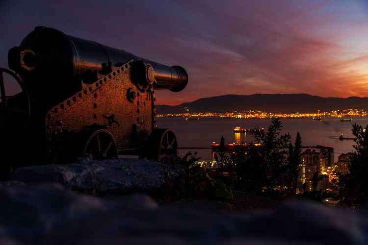 Cannon in city against sky during sunset