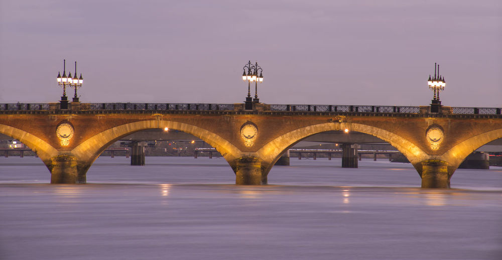Arch bridge over river at dusk