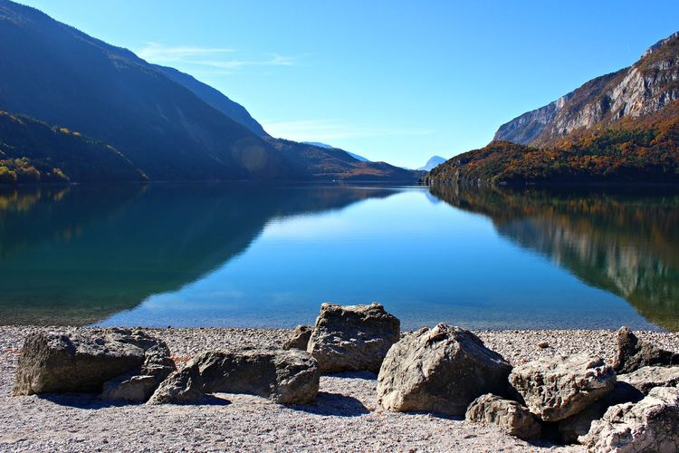 Italy, Trentino: View of Molveno Lake. Autumn Beautiful Reflection Trentino Alto Adige Wonderful Beach Horizon Italy Lake Landscape Molveno Mountain Nature No People Outdoors Reflection Reflection Lake Road Holidays Rocks Sky Stones Tranquil Scene Tranquility Tree Water