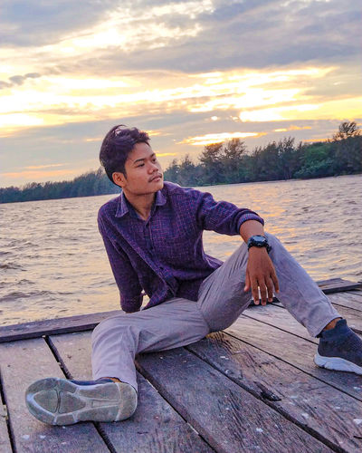 Young man sitting on wood against lake during sunset