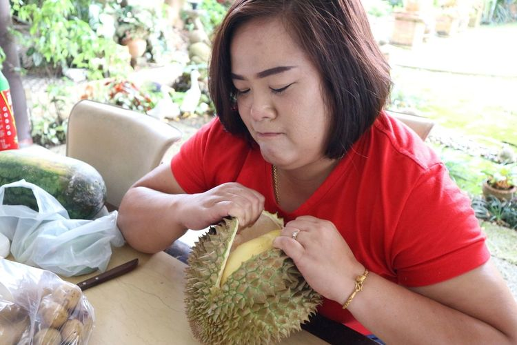 Woman opening durian on table sitting in yard