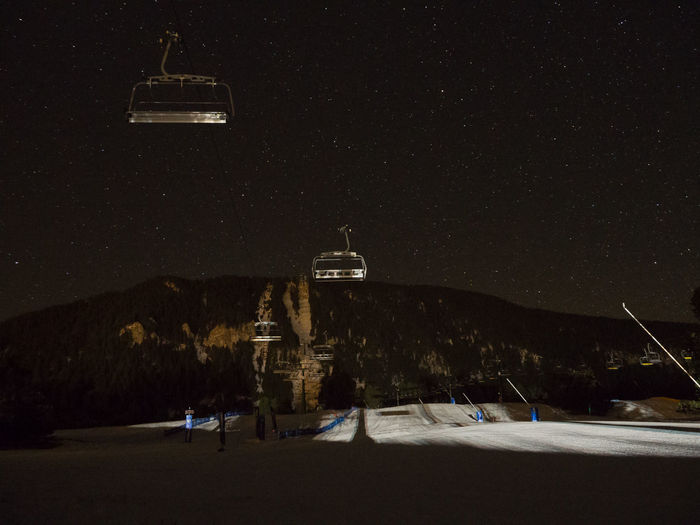 Ski Lifts Over Snow Covered Field By Mountain At Night