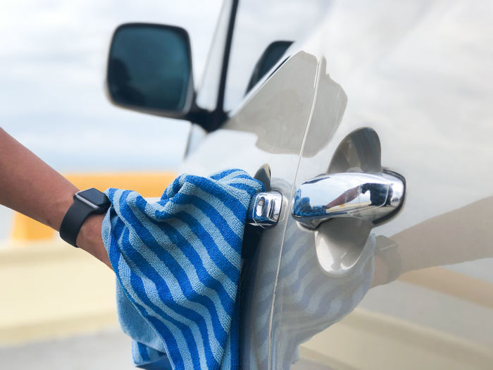Close-up of hand cleaning car