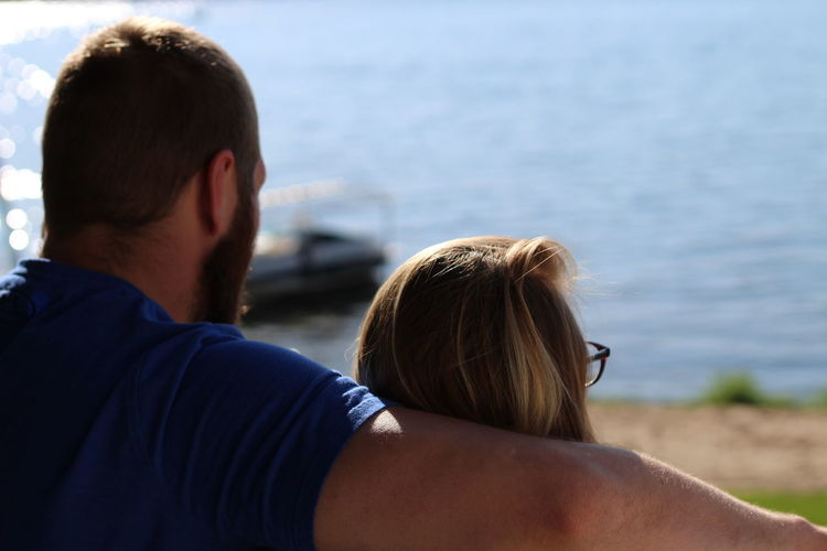 Rear view of couple standing at beach during sunny day