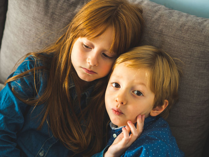High angle view of siblings sitting on sofa at home