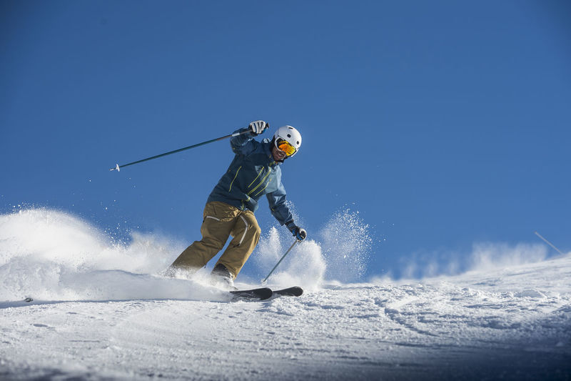 Low angle view of person skiing on snow against sky