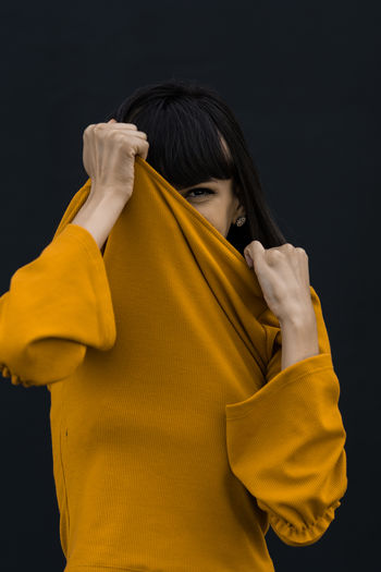 Portrait Of Woman Covering Face With Top Against Black Background