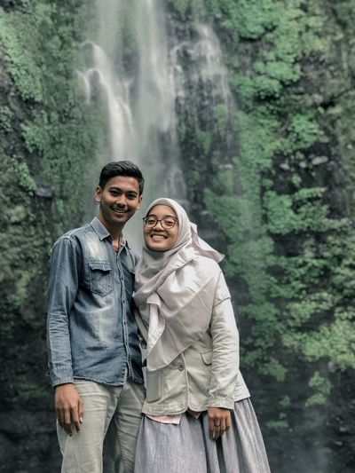 Portrait of couple smiling while standing against waterfall
