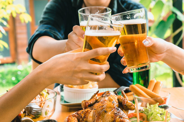 Food And Drink Drink Refreshment Glass Human Hand Alcohol Real People Drinking Glass Lifestyles Table Women Freshness Food Celebratory Toast Group Of People Hand Household Equipment Friendship Beer Human Body Part Drinking
