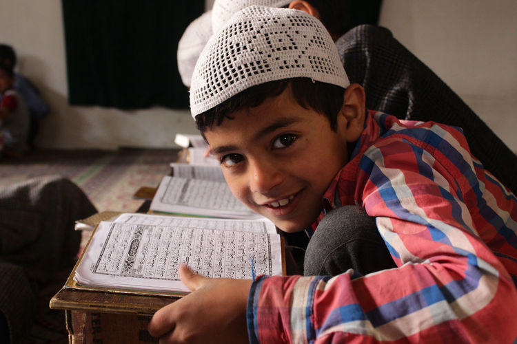 Portrait of smiling boy with quran