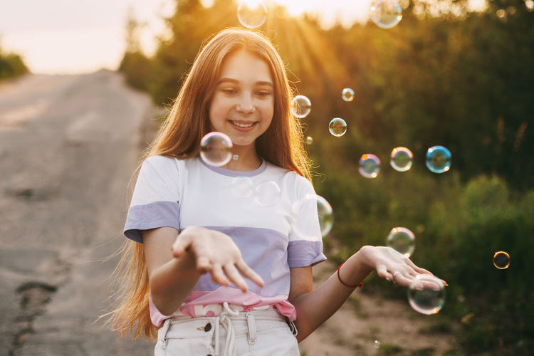 Portrait of smiling girl playing with bubbles in park during sunset