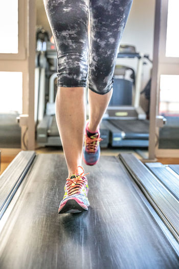 Close up of woman legs in colorful shoes running on treadmill machine in gym. Fast training indoor. Healthy active lifestyle concept. Woman Gym Exercising Females Girl Running Bicips Tapis Roulant Athlete Sport Press Machine Training Trainer Triceps Legs Lifestyles Healthy Biceps Muscles Indoors  Body Part Human Body Part Healthy Lifestyle Indoors  Human Leg One Person Low Section Adult Shoe Sports Clothing Women Clothing Sports Training Human Limb Vitality Limb Effort Exercise Machine Human Foot Self Improvement
