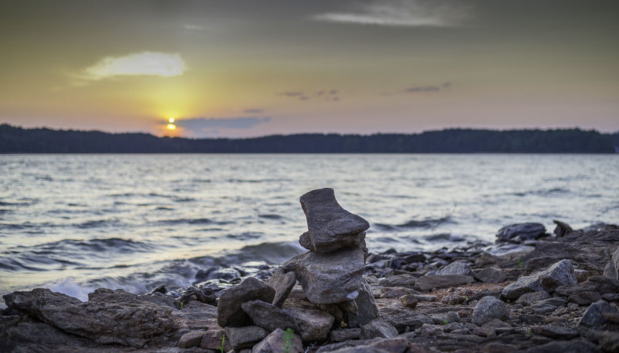 Close-up of rocks at shore against sky during sunset